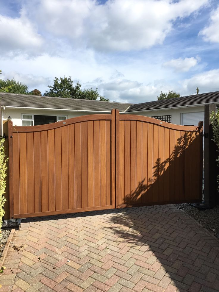 """Hardwood entrance gate from our """"Berkshire"""" collection. Double swan header, deep framed with vertical iroko cladding. This one was fitted by us with an underground automation system and finished with a simple wax. An elegant and traditional wooden gate design."""