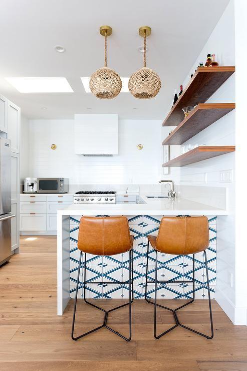 Le bois des étagères murales et le cuir des chaises hautes contrastent joliment avec le revêtement