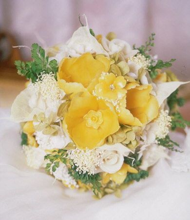 The center of Hopelessly In Love consists of large garden tulips, mini daffodils and primrose.  Surrounded by ivory roses and calla lilies.  Soft fern and hydrangea cushion the beeswax. preserved fresh flowers.