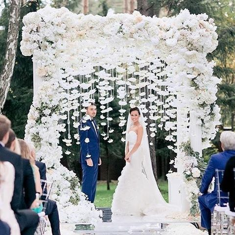 A white wedding ceremony setup that made our hearts skip a beat! The serene snow white arch, luscious overgrown flower garland, and dazzling crystal strand are all you need to create this utterly romantic and enchanting setup! Perfect for couples who want a garden themed wedding #inspiration #allwhitewedding