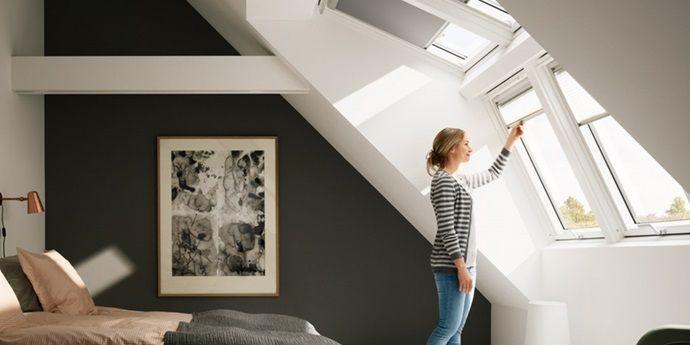 Vrouw in slaapkamer kijkt uit raam