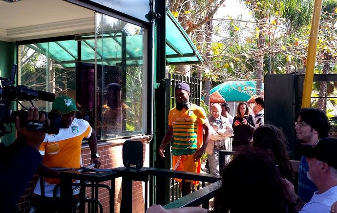 """Os torcedores que fizeram plantão em frente ao Oscar Inn, em Águas de Lindoia, foram surpreendidos neste sábado com a presença de ninguém menos que Drogba. O atacante aproveitou o período de descanso para """"escapar"""" da concentração e atender quem estavam do lado de fora, comprovando mais uma vez por que ganhou o rótulo de """"rei do carisma"""" dos fãs locais.  É uma alegria enorme estar no Brasil e poder ficar próximo dos fãs."""