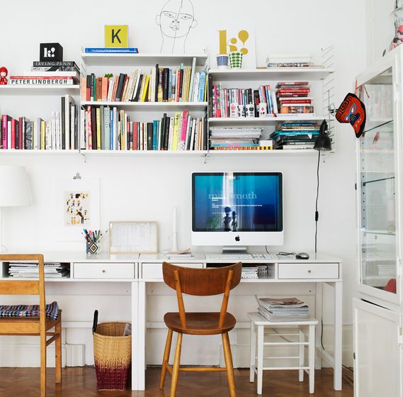 Dual office space. White desks, shelves and walls. Bright books and accessories. Eclectic yet clean look.