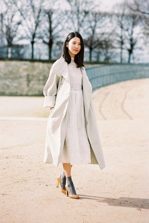 A white high neck midi dress is worn with a long trench coat, grey socks and brown pumps.