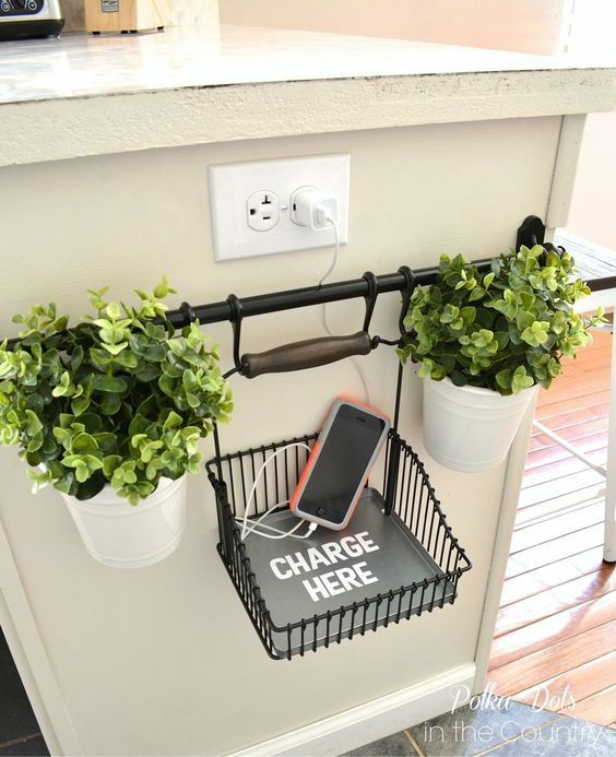 To keep electronics from cluttering your counter, you can mount this bar near an outlet along with a basket to hold your gadgets. This blogger even added potted plants for decoration.