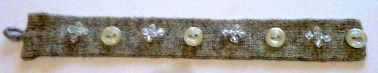 Braccialetto realizzato con un pezzo di cintura di lana e decorato con bottoni e piccole perline trasparenti.