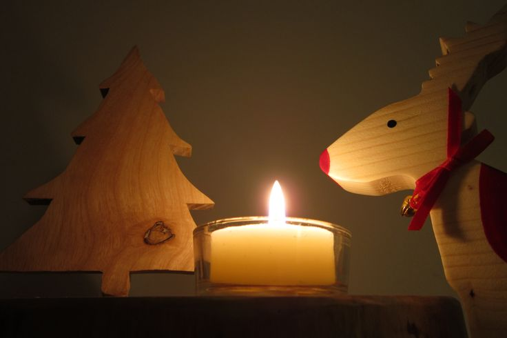 Wooden Christmas tree on wooden base with tealight. Standing reindeer on right.