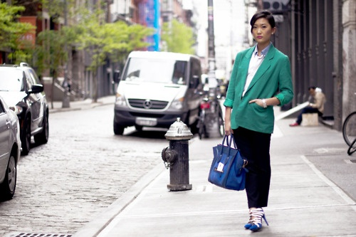 She pulls off a green blazer with style in minimal  makeup and bright blue bag.