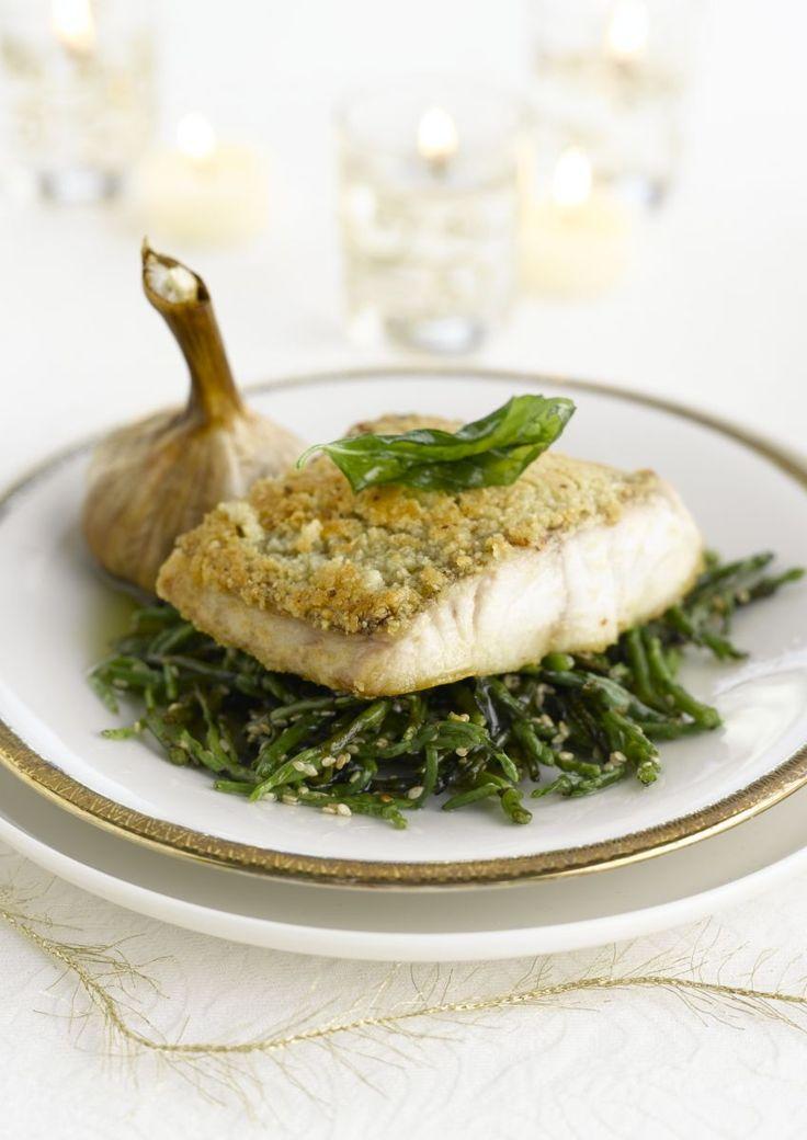 bereiden:Meng de olijfolie met de fijngesneden basilicum en laat minimaal 4 uur trekken.Leg de hele knoflookbollen in een ovenschaal en bestrijk ze rijkelijk met olijfolie. Bak ze ongeveer 15 minuten in de oven op 180° C, tot de bollen gaar zijn. Houd ze warm.Verdeel de zeebaars in zes mooie stukken en kruid ze met peper en grof zout. Bak de vis in hete olie met de velkant naar boven. Verdeel het amandelpoeder over het vel van de vis en keer de stukken voorzichtig. Bak de vis op zacht vuu...