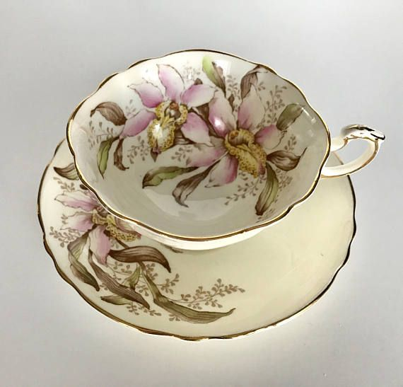 Vintage Paragon china tea cup, saucer and plate made in England. A butter yellow ground with beautiful white and pink orchids on both the cup and saucer. Both pieces are in good condition, no chips, cracks or crazing. Please Note: The items I sell are not new, they are vintage or