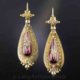 Two and seven-eighths inches long, lavish and ultra-lovely Victorian ear drops, circa 1875, hand-fabricated in warmly patinated 18K gold. Delicately ornamented with micro beading, fine torsade wire work and white enamel accents, the earrings center elongated pear shape cabochon garnets crowned with sparkling diamond stars. Rare and ravishing originals with some virtually imperceptible (with the naked eye) damage to the enamel on the upper half of one earring (priced accordingly). Splendid!
