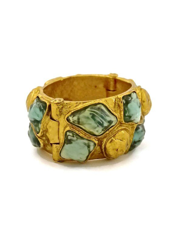 84c6b76f1d5 Textured cuff bracelet studded with blue irregular cabochons. - Signed YSL.  - Pin closure. - Gold tone. - Excellent vintage condition.