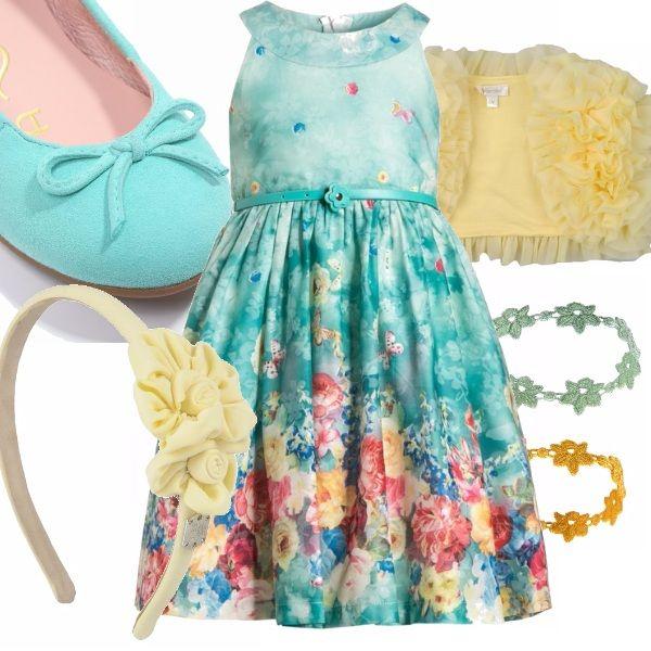Un outfit dai colori estivi per una cerimonia o un evento particolare da vivere da protagonista. L'abito fantasia è abbinato da un coprispalle dalla lavorazione particolare. In tinta anche gli accessori che completano il look.