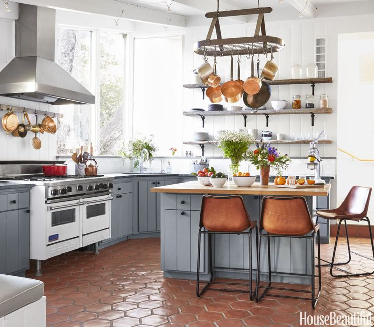 Frances Merrill kept an Oaji home's existing countertops and white Viking range but gave the base cabinets a more relaxed vibe with new doors painted in Benjamin Moore's Duxbury Gray. She also installed hexagonal terra-cotta floor tiles and open shelves of reclaimed wood. CB2 counter stools in leather reflect the decision to focus on natural materials.