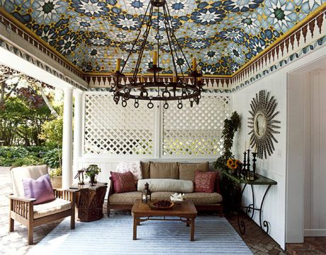 The pool house's ceiling and border were inspired by a Moroccan tile mosaic. Artisans painted it on beadboard for a tentlike effect. Bell made the batik pillows from an Urban Outfitters bedspread. The striped rug is from the Wisteria.