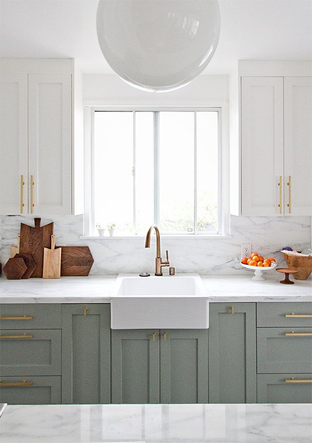 White kitchen with sage cabinetry and marble counters