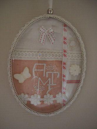 """Ravissant cadre oval avec son verre bombé. Il est recouvert d'un tissu rose tendre brodé avec un monogramme, de la dentelle, un ruban avec des lettres """"PG"""", un nœud, un bouton t - 15926594"""