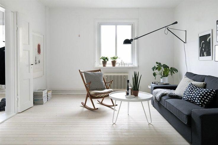 Белая гостиная в скандинавском стиле (Göteborg): белые стены и потолок, белое напольное покрытие, черный диван, кресло качалка, черно-белые подушки с геометрическим принтом