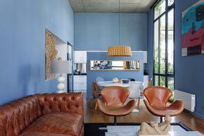 Living comedor con cocina sutilmente integrada, sectorizada por un panel con espejo. Azul cerúleo o calipso con matices grises en combinación con el marrón del cuero y la madera.