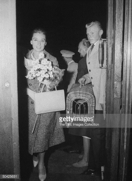 Actress Audrey Hepburn holding her dog Famous & bouquet of daisies as she enters hotel where bell boy holds dog's traveling case, which contains pair of shoes.