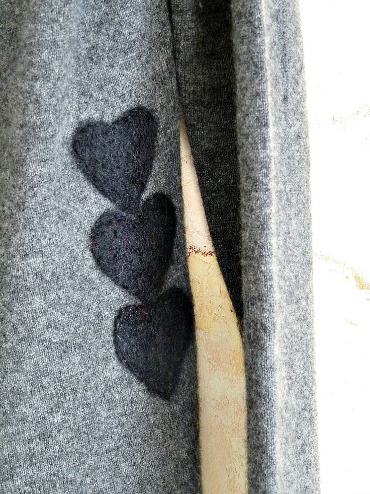 Detail of easy DIY felted wool appliques that fix a small sweater hole and give this plain sweater a sweet new look