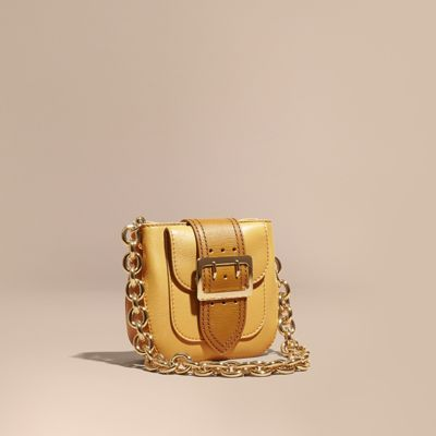 The Buckle Bag – Square in grainy and textured leather, inspired by military…