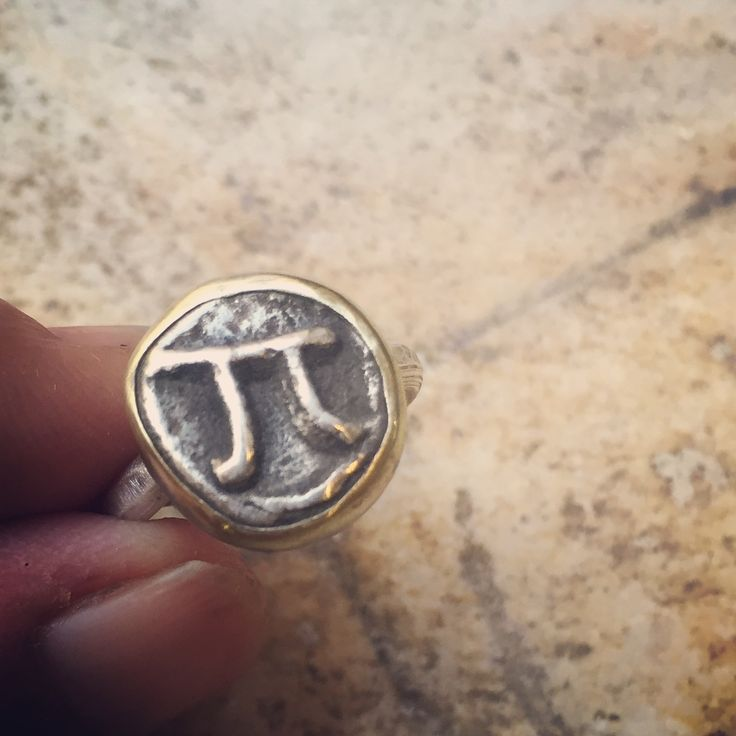Silver Π 'coin' ring minted in charcoal with brass bezel