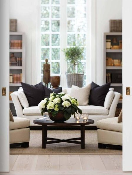 White sofas, white large windows, simple bookshelves, black accent pieces. Love! (no source).
