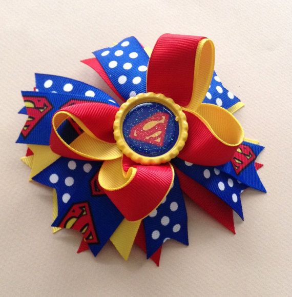 Superman Hair Bow   • 3 layers • 5 inches across approximately • Bottle cap embellishment • Alligator Clip. ( can be changed to French Barrete clip upon request) Also available on a stretchy headband ( please message me). • All ribbon ends are heat sealed to prevent fraying • Handmade item. Like me on Facebook : www.facebook.com/AurorasChicBowtique