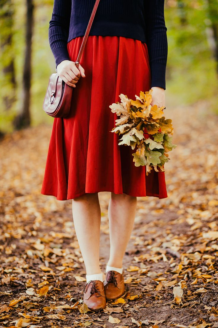 neavy blue crop sweater layered over a rusty red midi dress