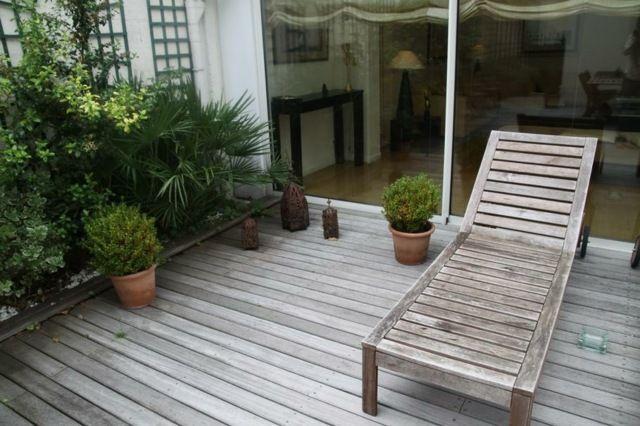 Décoration végétale et une chaise longue en bois