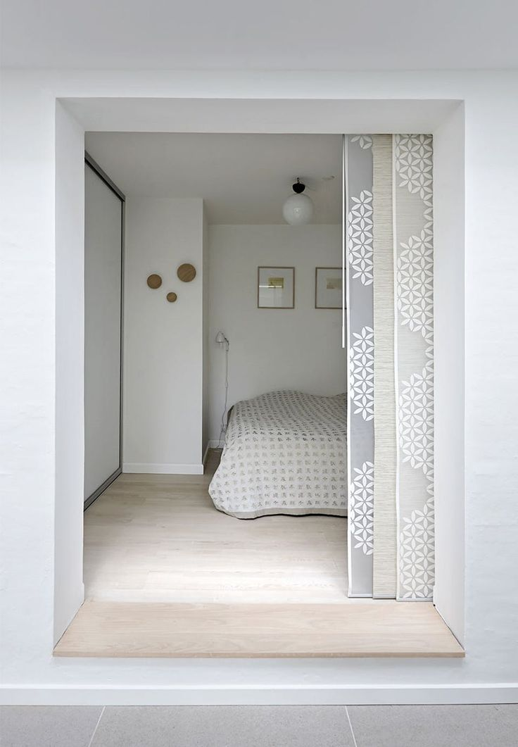 Simply decorated bedroom in a small space. The fitted wardrobes with sliding doors provide plenty of storage without stealing the site. Sliding curtains are from Ikea, wooden hooks from Muuto, bedspread brought home from China.