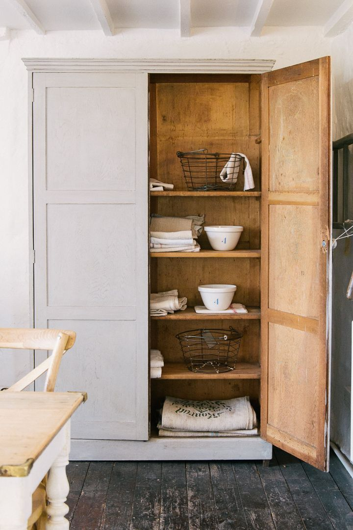 a gorgeous antique cupboard filled with baskets and bowls and linens