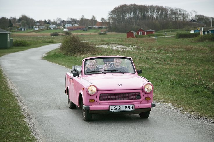 John and the pink Trabbi acting as taxi for a beach wedding. danish destination wedding planner on the beautiful island of aeroe. www.getmarriedindenmark.com  photo by www.camillajorvad.com
