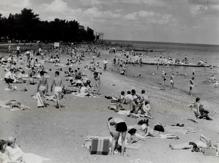 Crowded beach is on the lake side of Centre Island; a popular spot as Toronto's thousands sought cooling breezes and water as they enjoyed the line; hot week-end weather. Ideal summer weather lured huge crowds to all of Toronto's beaches and sent other thousands driving out into the country for picnics and other country activities.