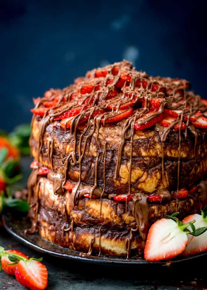 Tall image of a four layer chocolate bread and butter pudding round cake on a black plate. Nutella and strawberries on the top and in the middle. Cake is slightly cropped on the right hand side. Dark blue background, strawberries scattered around.
