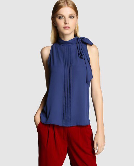 Blusa en color azul con detalle de jaretas, sin mangas, con cuello alto y adorno de lazo.