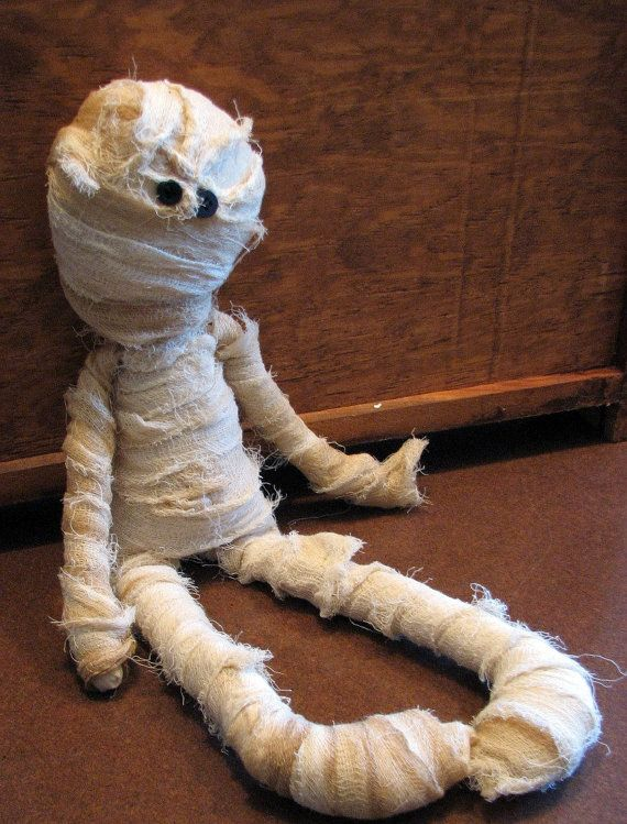 This Raggedy Mummy Doll will stand out on your shelf or mantle this Halloween season. Measuring approximately 18 inches long, made from a muslin body,