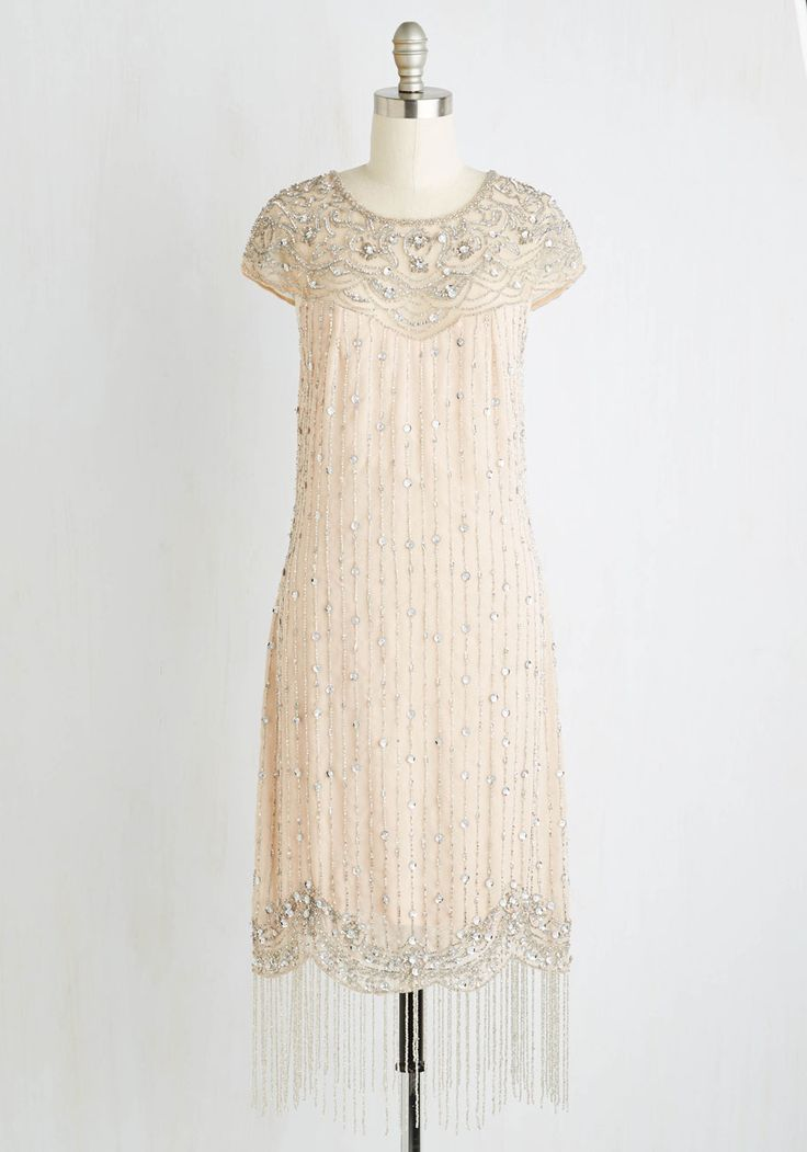 This beige sheath dress stars an illusion neckline bedecked in beads and rhinestones, a vertically striped silhouette sprinkle with sequins, and a scalloped hem with sparkling tassels.