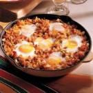 "Sheepherder's Breakfast: 1 lb bacon diced, 1 med onion, chopped; 32 oz shredded hash brown potatoes, thawed; 10 eggs; salt & pepper.  In large skillet, cook bacon & onion until bacon is crisp. Drain all but 1/2 c of drippings. Add hash browns; mix well. Cook over med heat for 10 min, turning when browned. Place 1 egg in each of 10 ""wells"" evenly spaced in hash browns. Sprinkle with salt & pepper. Add cheese if desired. Cover and cook over low heat for about 10 minutes or until eggs are set."