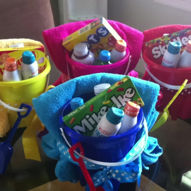 A girls beach weekend gift basket - towel, bucket, sunscreen, pest repellent, aloe vera, candy and a bottle of flavoured water wrapped up with matching bow!