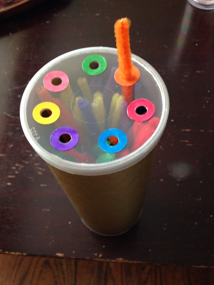 DIY pipe cleaner colour sorting activity. Empty Pringles can covered in wrapping paper, punch holes in lid and add coloured 3 ring hole reinforcers.
