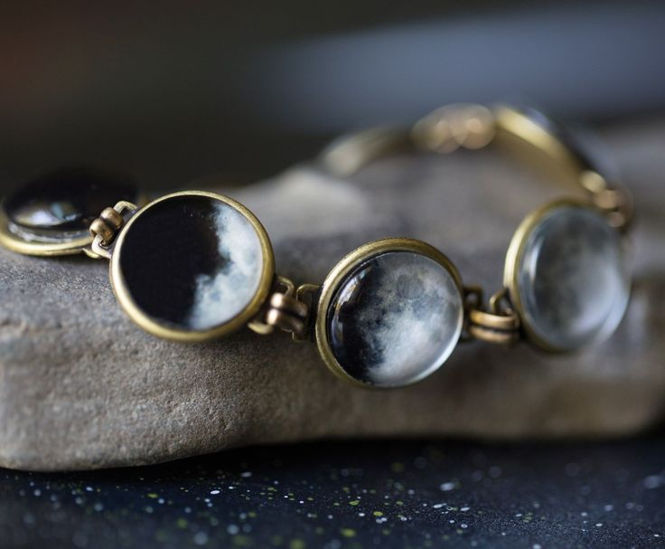 """Images depict seven lunar phases from crescent to full and back to crescent Images are 14mm in diameter Bracelet measures 7 3/4"""" (19.7cm) long Antique silver tone Made in Maryland, USA A great gift for anyone who loves space.  Please note that these are not 100% waterproof, so please remove before showering, swimming or submerging your hands in water. Some images show antique bronze tone. This item is antique silver tone.  Image credit Kristi Woody from Woody and Pearl Photography"""