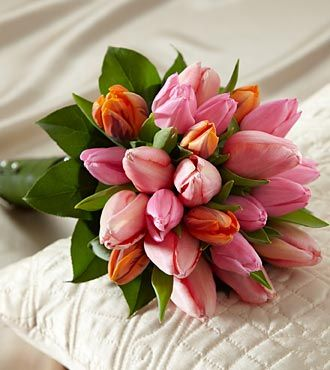 Embraceable Bouquet is perfect for a spring wedding, but gorgeous at any time of the year. Salmon French Tulips are brought together with fuchsia and bi-colored orange tulips and tied together with fresh ti leaves at the stems, accented with silver pixie pearl pins for an exquisite look, $159.99.