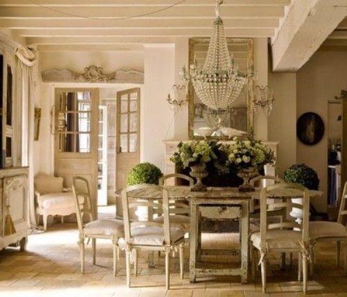 French country cottage blends traditional and farmhouse elements. a crystal chandelier, hangs above a worn painted farmhouse table and delicate wall sconces adorn the fireplace. Flowers and greenery add dots of color to the monochrome color theme.