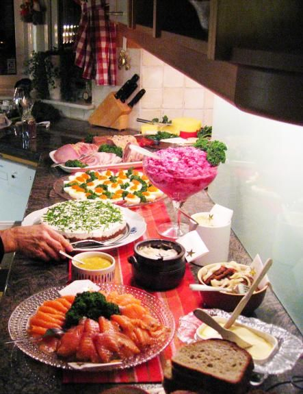 a swedish julbord (christmas table) usually pickled sill (herring) and varmrokt lax (smoked salmon) are   served along with a traditional ham