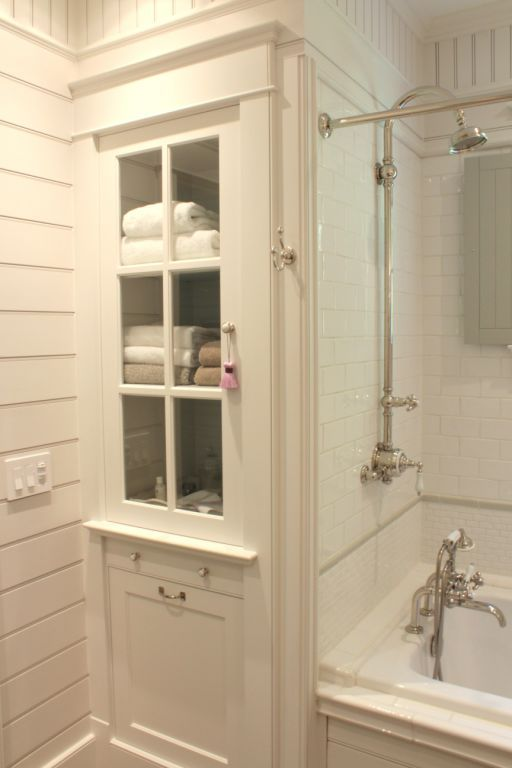 bathroom linen cabinet and tub surround with white subway tile the