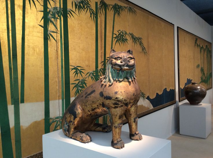 Art Antiques London 2014 One of the pair of komainu (guardian dogs), Japan. In the background detail from a pair of six-fold screen with bamboo on gold, Japan, 18th c