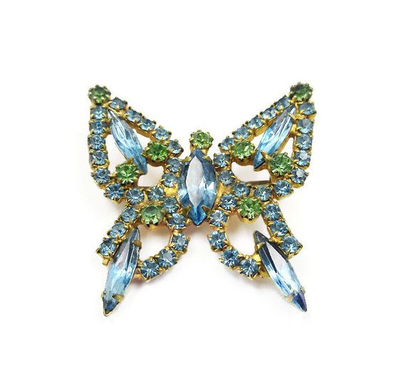 Vintage butterfly brooch with blue and green rhinestones. All stones are prong set in a gold tone metal setting. Age: estimated circa 1950s - 60s Measurements: it is approximately 1-3/4 tall x 1-5/8 wide. Condition: it is in overall very good condition. There is light wear consistent with age. The clasp on the pin back closes securely.  We offer free shipping within the United States. International shipping rates are as listed.  To see more vintage brooches: https://www.et...
