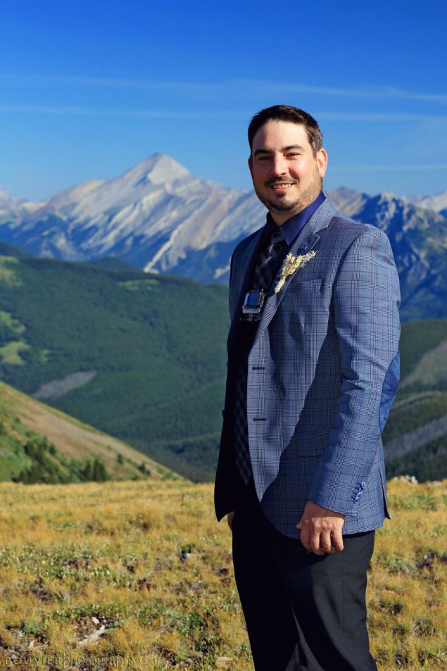 Best man in mountain top wedding in Canmore Alberta. Best man standing on top of mountain. Summer heli-wedding. Canmore Alberta wedding.